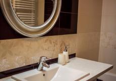 łazienka, mieszkanie wzorcowe - umywalka z lustrem oraz wanna z prysznicem (Lokum da Vinci)