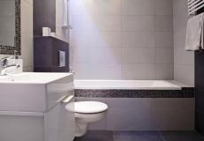 łazienka w mieszkaniu wzorcowym - wanna, toaleta i umywalka (Lokum da Vinci)